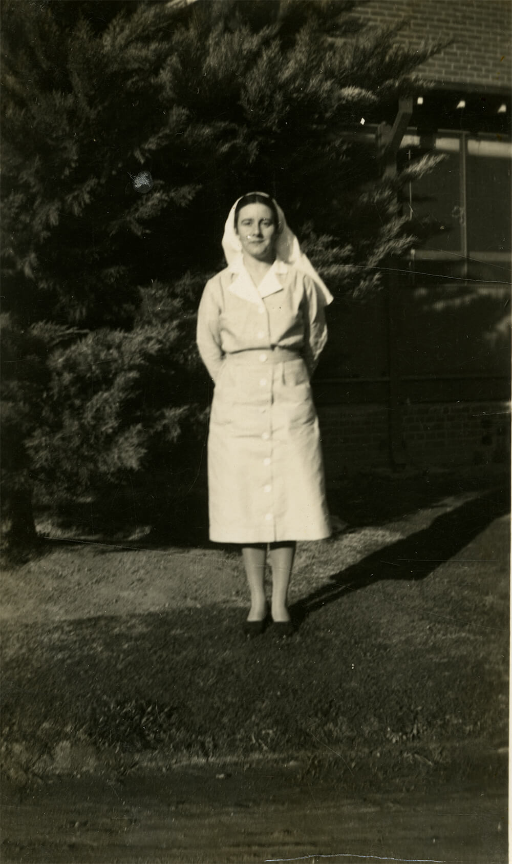 Black and white photograph of nursing sister (Sister Tamplin ) standing in garden at Albury District Hospital, 1930. ARM 12.216.01.