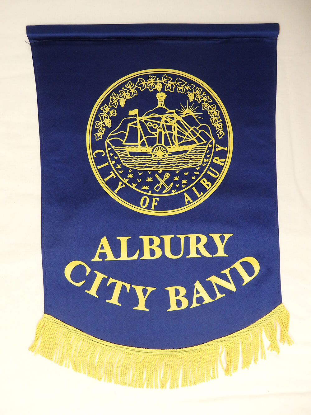 A music stand banner, from the Albury City Band. Blue leather with gold fringe on the bottom. ARM 90.106.