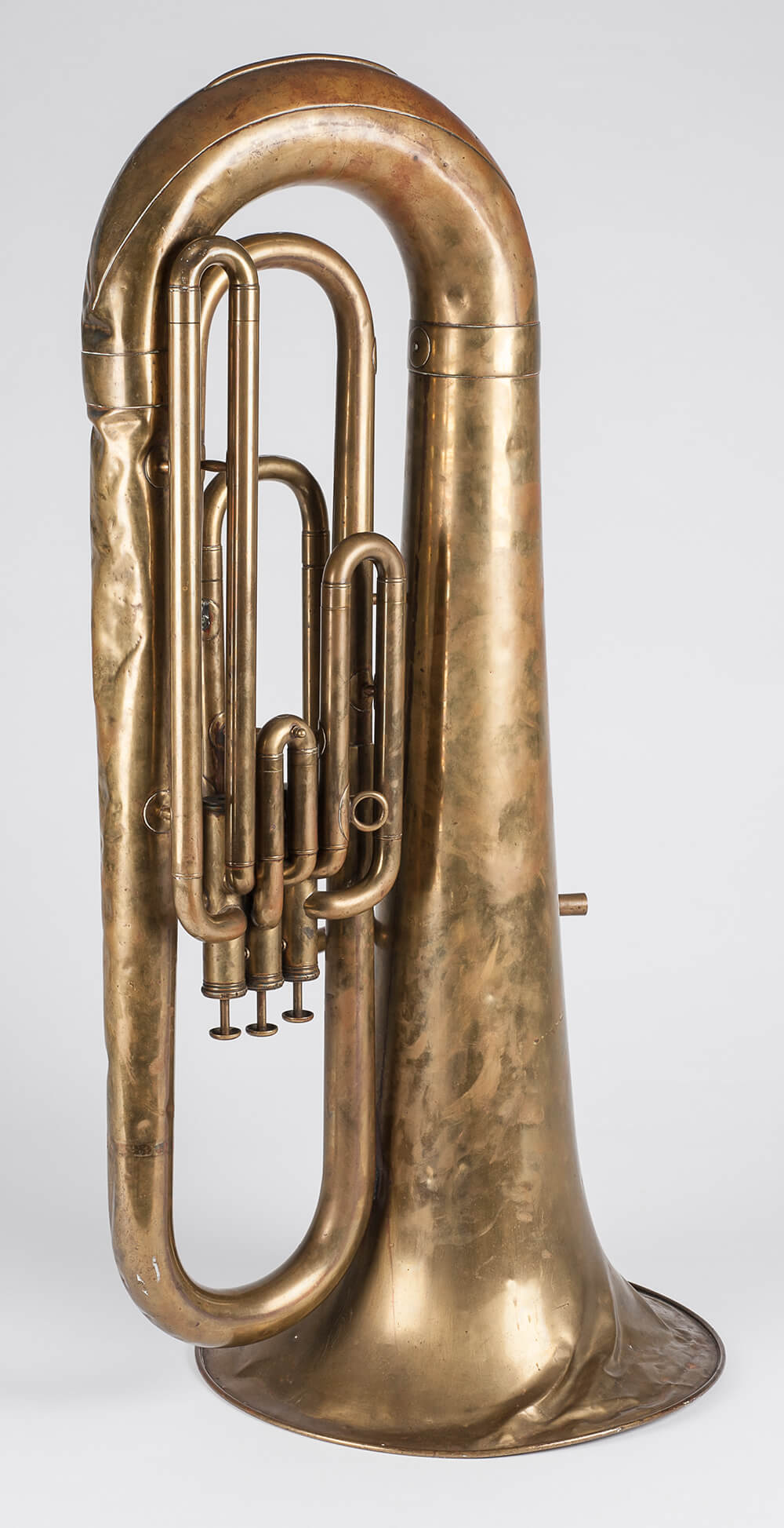 A euphorium. Mouth piece missing, silver in colour. Has three keys, with a leaf pattern on the trumpet end. ARM 90.107.