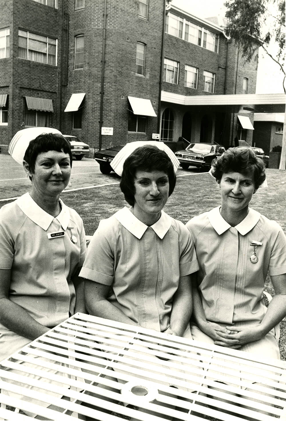 Black and white photograph of three nurses sitting at a garden table in front of the Abury Base Hospital. From left: Nurses Baker, Gugger and Frohling. Nurses Baker and Frohling wearing nametags and watches pinned to uniforms, 1975. ARM 12.377.01.