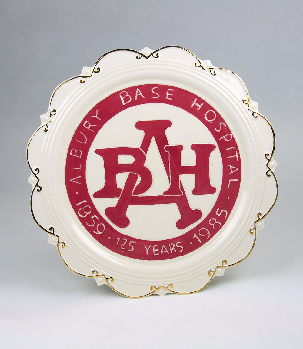 Cream and red ceramic plate with gold piping on edge, made to celebrate the 125th anniversary of Albury Base Hospital in 1985. Plate has