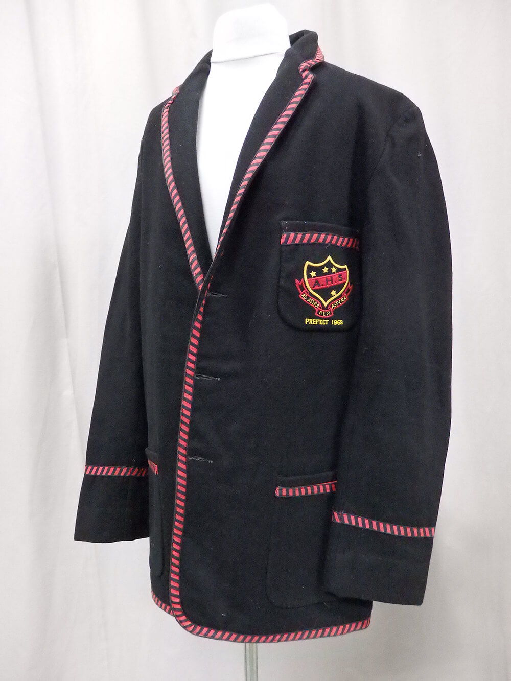 A navy blue Albury High School prefects blazer from 1968. The school crest and motto are embroidered on the left breast pocket. The blazer has three pockets and three buttons. Red and black striped edging is sewn on pockets, cuffs and around edges. ARM 94.009.